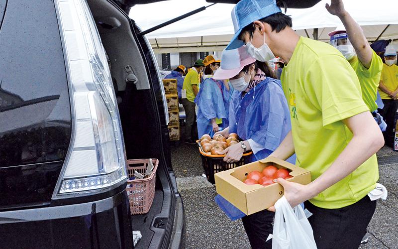 商品をお客さまの車に積み込む職員